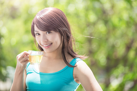 hot drink: Beautiful Young Woman drinking green tea with nature green background, healthy lifestyle concept, asian beauty