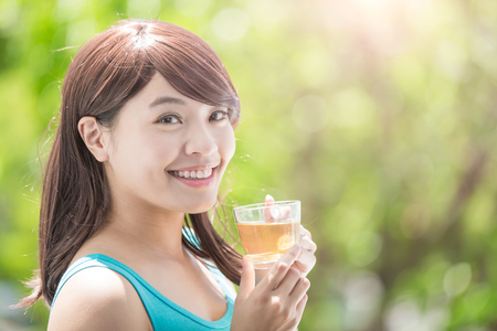 forest tea: Beautiful Young Woman drinking hot tea with nature green background, healthy lifestyle concept, asian beauty Stock Photo