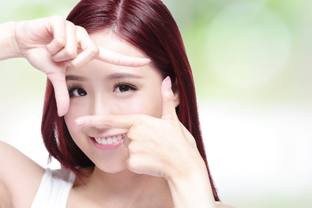 green eyes: Woman face and eye care and she making frame with hands, asian woman Stock Photo