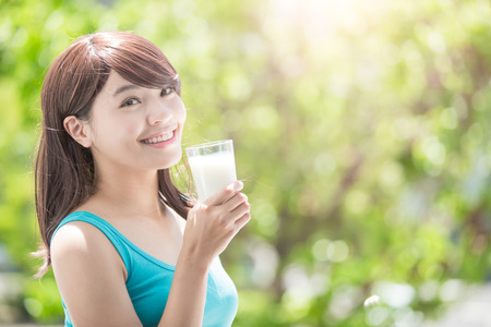 woman drinking milk: Beautiful Young Woman drinking milk with nature green background, healthy lifestyle concept, asian beauty