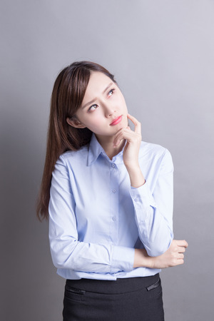 asia people: Thinking business woman and look copy space isolated on grey background with finger at face, asian beauty Stock Photo