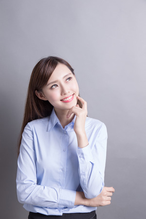 Thinking business woman and look copy space isolated on grey background with finger at face, asian beauty Stock Photo