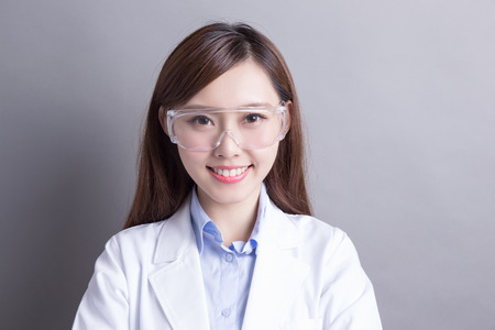 Lachende Frau Labortechniker auf grauem Hintergrund, asiatisch