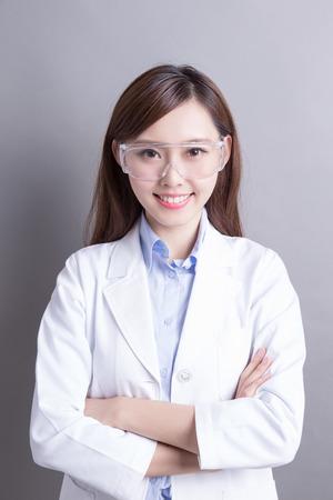 Glimlachende vrouw laborant geïsoleerd op grijze achtergrond, Aziatische