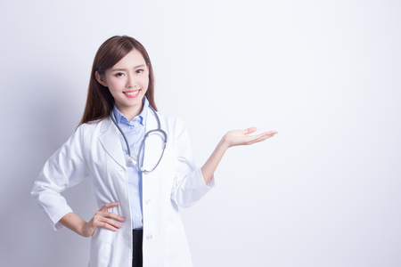 Smiling medical doctor woman with stethoscope show something. asian