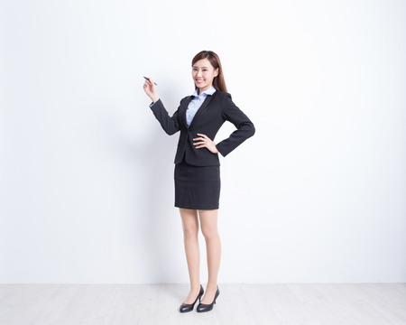 full length woman: business woman writing something on white wall background, great for your design or text, asian