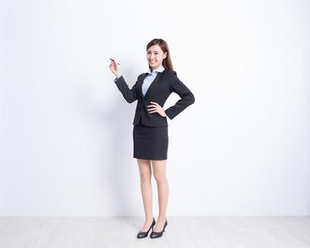 mujer cuerpo entero: mujer de negocios escrito algo en el fondo de la pared blanca, perfecto para su dise�o o texto, asi�tico