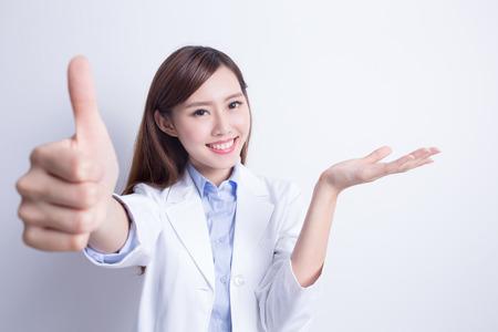 buena salud: Mujer sonriente médico mostrar algo a usted. Aislado sobre fondo gris. asiático Foto de archivo