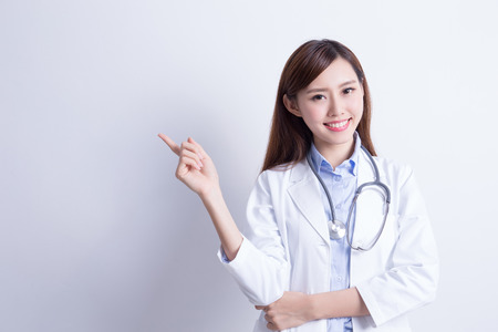 Smiling medical doctor woman show something to you. Isolated over gray background. asian