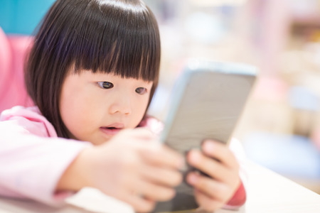 child girl happy look smart phone. asian child Stock Photo
