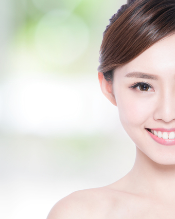 Half portrait of the woman with beauty face, perfect skin and health teeth, she smile to you with nature green background, asian beauty