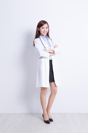 Lachende medische arts vrouw met stethoscoop. Met witte muurachtergrond. Aziatisch