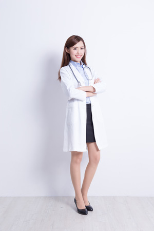Smiling medical doctor woman with stethoscope. with white wall background. asian