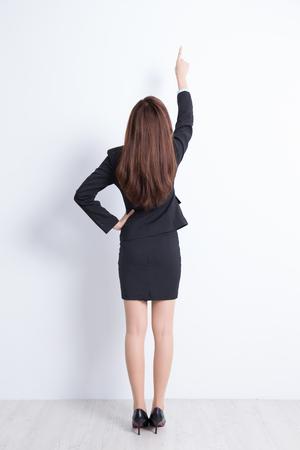 Achter mening van het bedrijfsleven vrouw wijzend witte muur achtergrond, geweldig voor je ontwerp of tekst, Aziatisch Stockfoto
