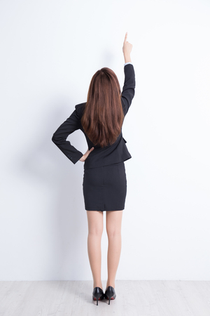 back: Back view of business woman pointing white wall background, great for your design or text, asian