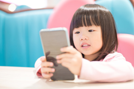 child girl happy look smart phone. asian child Stock Photo