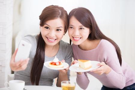 ni�a comiendo: Dos felices j�venes amigas toman foto autofoto por tel�fono inteligente, con tazas de caf� y pasteles en la sala de estar en casa, el concepto de estilo de vida saludable, belleza asi�tica