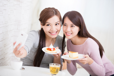 coffee and cake: Two happy young female friends take selfie picture by smart phone, with coffee cups and cakes in the living room at home, healthy lifestyle concept, asian beauty