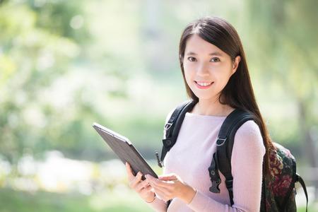 estudiante: Estudiante de mujer joven sonríe con la tableta digital. la naturaleza de fondo verde, belleza asiática