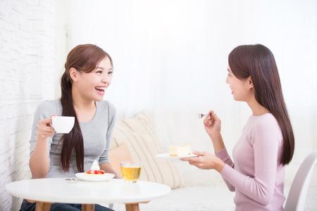 Due giovani amici femminili con tazze di caffè e torte godendo di una conversazione in salotto a casa, sano concetto di stile di vita, asiatico bellezza