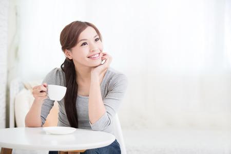 tarde de cafe: sonreír joven sosteniendo la taza mujer de café o té en su casa, el concepto de estilo de vida saludable, belleza asiática, belleza asiática Foto de archivo