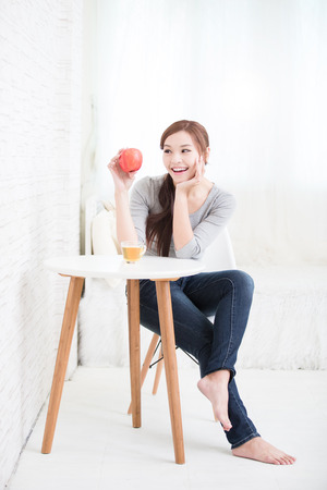 tea table: woman hold red apple at home, healthy lifestyle concept, asian beauty Stock Photo