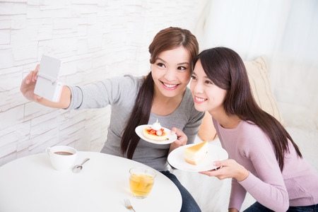 afternoon break: Two happy young female friends take selfie picture by smart phone, with coffee cups and cakes in the living room at home, healthy lifestyle concept, asian beauty
