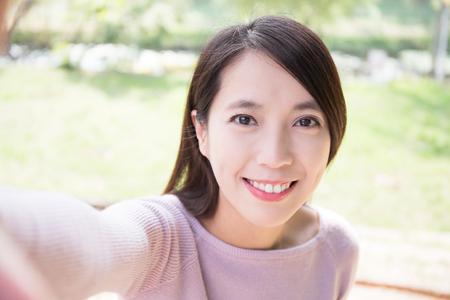 junge Frau Lächeln nehmen selfie. Natur grünen Hintergrund, asiatische Schönheit