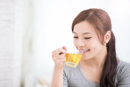 sorria jovem mulher segurando a xícara de chá verde em casa, conceito de estilo de vida saudável, beleza asiática, beleza asiática Foto de archivo
