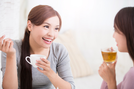 Twee gelukkige jonge vrouwelijke vrienden met kopjes koffie en gebak genieten van een gesprek in de woonkamer thuis, gezonde leefstijl concept, Aziatische schoonheid