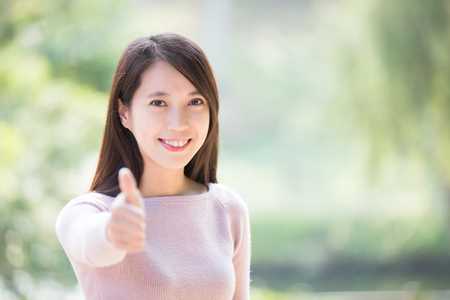 asian lady: young woman smile show thumb up gesture. nature green background, great for your design, asian beauty