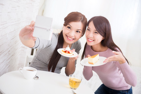 tea break: Two happy young female friends take selfie picture by smart phone, with coffee cups and cakes in the living room at home, healthy lifestyle concept, asian beauty