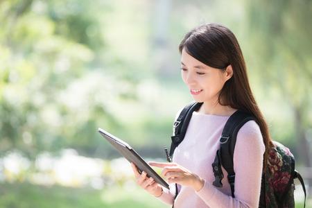 junge Frau Student mit digitalen Tablet-Lächeln. Natur grünen Hintergrund, asiatische Schönheit