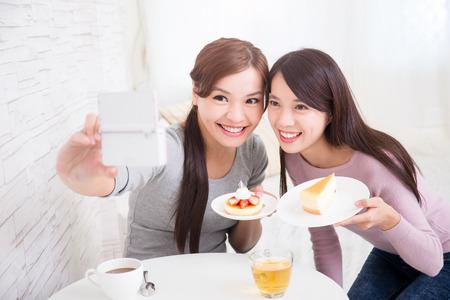 niñas chinas: Dos felices jóvenes amigas toman foto autofoto por teléfono inteligente, con tazas de café y pasteles en la sala de estar en casa, el concepto de estilo de vida saludable, belleza asiática