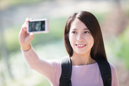 student travel: young woman traveler happy smile take selfie. nature green background, asian beauty Stock Photo