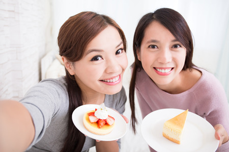 self care: Two happy young female friends take selfie picture with coffee cups and cakes in the living room at home, asian beauty