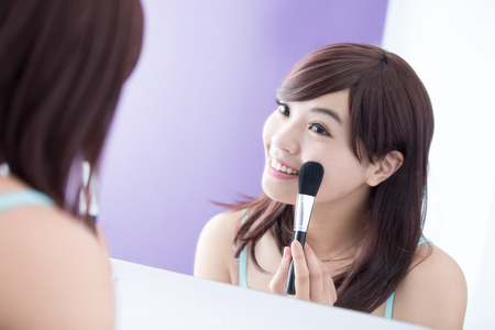 make up brush: Close up of Smile woman with makeup brushes near face and look mirror. asian beauty Stock Photo