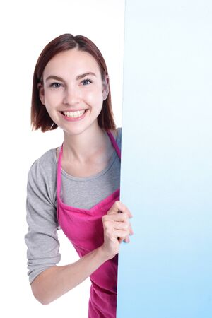 billboard background: Happy young woman housewife showing empty billboard Wearing Kitchen Apron Over White Background, caucasian