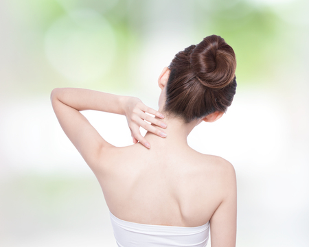 Woman massaging pain back and shoulder with nature green background, asian
