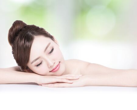 charming girl: Charming woman face Smile enjoy spa and massage while lying with green background, asian girl