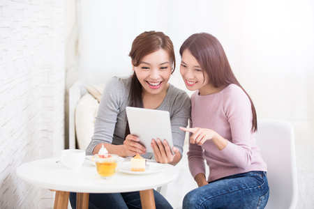 Two happy young female friends use digital tablet pc with tea, coffee and cakes, healthy lifestyle and tecnology concept, asian beauty Фото со стока