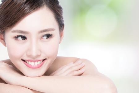 dientes: Cara de la mujer encantadora sonrisa para cerrar arriba mientras est� acostado con la naturaleza de fondo verde, muchacha asi�tica Foto de archivo
