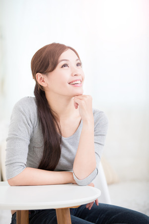carefree: smile young woman sit and look or think something at home, healthy lifestyle concept, asian beauty