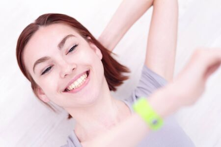 the caucasian beauty: Happy young smile woman look smart watch and relax lying on the wood floor, caucasian beauty Stock Photo