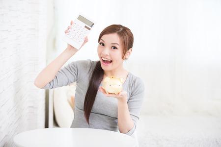 cuenta bancaria: sonrisa calculadora asimiento de la mujer y una hucha en casa, concepto de negocio, belleza asiática Foto de archivo