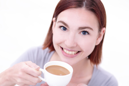 hot drinks: Close up portrait of a Happy young beautiful woman relax and drink coffee, caucasian beauty