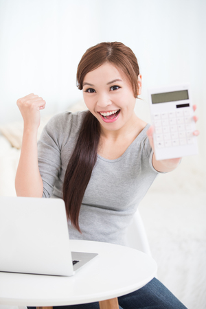 business money: smile young woman sit and hold calculator with laptop at home, business concept, asian beauty