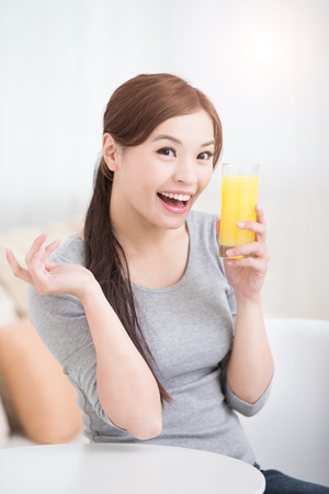 orange juice: Smile happy woman hold  orange juice at home, healthy lifestyle concept, asian beauty Stock Photo
