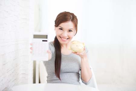 money in the bank: smile young woman hold calculator and piggy bank at home, business concept, asian beauty