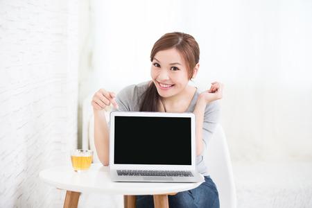 alzando la mano: sonrisa joven mujer de uso portátil y mostrar la pantalla vacía en casa, belleza asiática